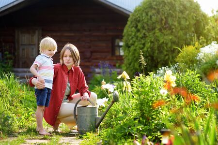 Cute little boy and his young mother watering plants in the garden at summer sunny day. Mommy little helper.