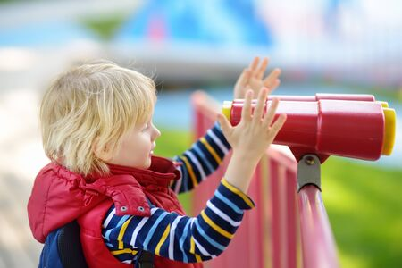 Cute little blond caucasian boy, kid or child looking through binoculars on playground outdoors. Activities and fun for children outdoors. Stock Photo - 124979082