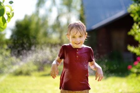 Funny little boy playing with garden sprinkler in sunny backyard. Preschooler child having fun with spray of water. Summer outdoors activity for kids. Stock Photo - 124979084