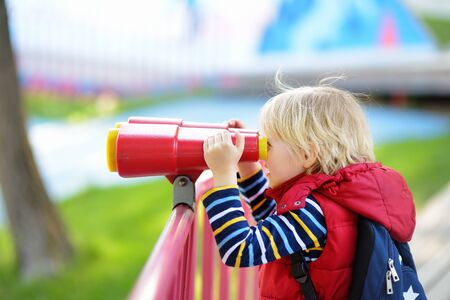 Cute little blond caucasian boy, kid or child looking through binoculars on playground outdoors. Activities and fun for children outdoors. Stock Photo