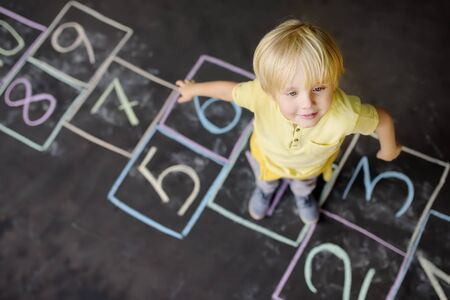 Little boy on hopscotch drawn on asphalt. View from the top. Child playing hopscotch game on playground outdoors on a sunny day. Summer activities for children. Stock Photo