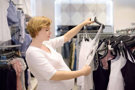 Young pregnant woman choosing underwear for breastfeeding in store. Shopping for expectant mothers and baby. Pregnancy and shopping. Stock fotó