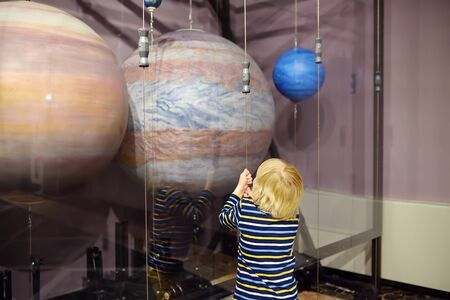 Little caucasian boy is looking an exposition in a scientific museum. Models of planets of the solar system. Education and entertainment for children. Activities for family with preschooler kids.