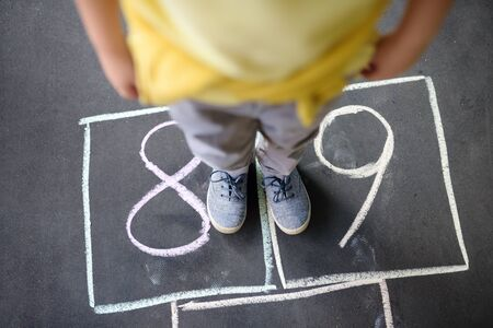 Closeup of little boys legs and hopscotch drawn on asphalt. Child playing hopscotch game on playground outdoors on a sunny day. Summer activities for children.