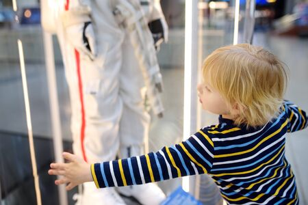 Little blond caucasian boy looking astronaut space suit in museum. Education and entertainment for children. Activities for family with preschooler kids. Stockfoto