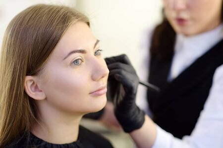 Beautician applying the tone of the foundation using special brush on face young beautiful model. Facial care and make up. Professional beauty salon