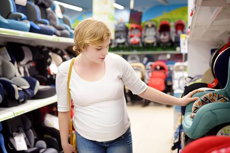Young beautiful pregnant woman carefully choosing infant car seat. Shopping for expectant mothers and baby. Pregnancy and shopping.