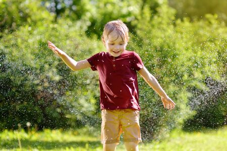 Funny little boy playing with garden sprinkler in sunny backyard. Preschooler child having fun with spray of water. Summer outdoors activity for kids. Stock Photo
