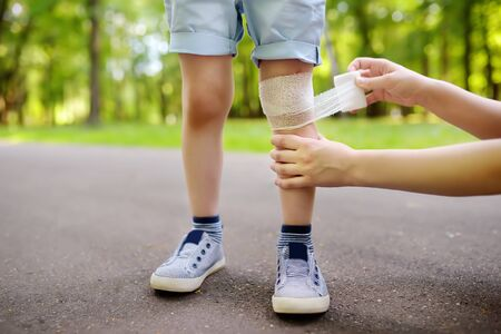 Mother hands applying antibacterial medical bandage on child's knee after falling down. First aid for kids after injury/trauma