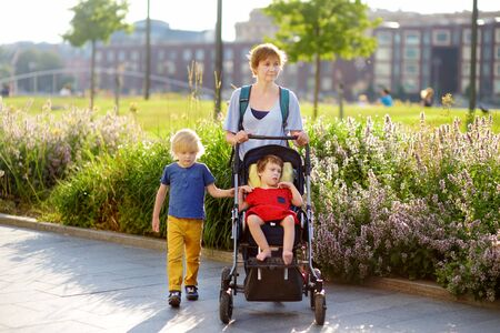 Woman with a boy and a disabled girl in a wheelchair walking in the park at summer. Child cerebral palsy. Inclusion. Family with disabled kid.