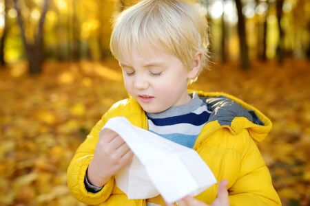 Little boy sneezing and wipes nose with napkin during walking in autumn park. Flu season and cold rhinitis. Allergic kid. Sick kids.
