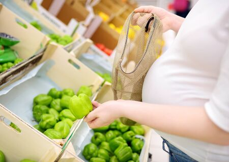 Young pregnant woman choosing fruits and vegetables in mesh shopping bag in supermarket. Concept of zero waste, recycling and protection environment.