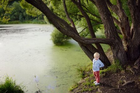 Upset or offended little boy standing on the shore of the pond. Child lose yourself. Escape from the house. Danger. Search for missing children.