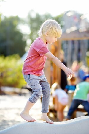Little boy having fun on playground of public park at sunny summer day. Active summer leisure for kids.