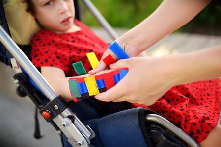 Mother puts orthosis on her daughter arms. Disabled girl sitting on a wheelchair. Child cerebral palsy. Inclusion. 免版税图像