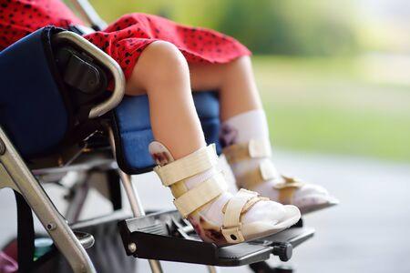 Niña discapacitada sentada en silla de ruedas. En su órtesis de piernas. Parálisis cerebral infantil. Inclusión. Familia con niño discapacitado.