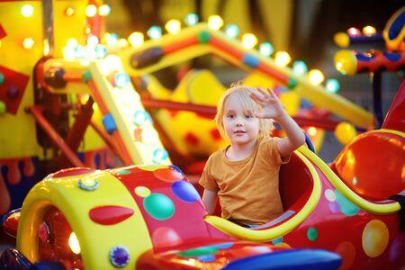 Niño divirtiéndose en la atracción en el parque público. Niño montado en un tiovivo en las noches de verano. Atracción, aviones, coches, iluminación, diversión ... Industria del entretenimiento.