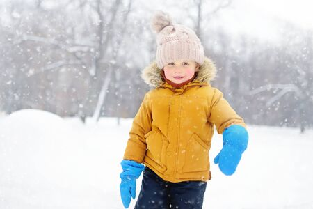 Cute little boy having fun in the snow. Outdoors winter activities for kids.