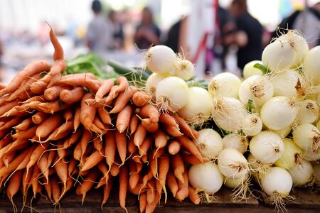 Fresh healthy organic carrots and onion on New York farmer agricultural market. Healthy vegetarian food. Standard-Bild - 129174577