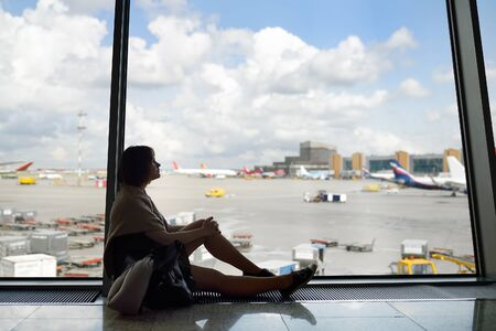 Woman with a backpack and a travel pillow sitting and looking on the plane in window on waiting area of the airport. Tourism and travel.