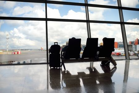 Passengers sitting and looking on the plane in window on waiting area of the airport. Tourism and travel.