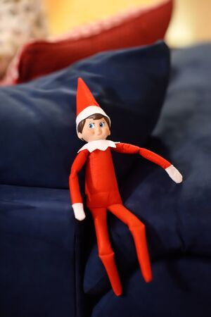 Funny Christmas toy elf on sofa. American christmas traditions. Xmas activities for family with kids.