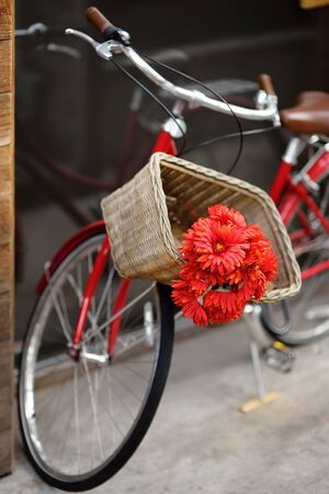 Romantic view of bike with bouquet of red flowers on street of town. A pleasant surprise. 写真素材