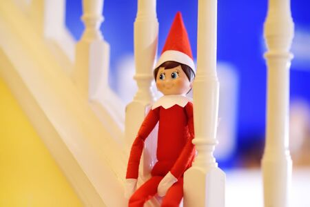 Funny Christmas toy elf on stairs. American christmas traditions. Xmas activities for family with kids. 写真素材