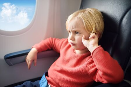 Capricious kid traveling by an airplane. Dissatisfied little boy sitting by aircraft window during the flight. Air travel with naughty kids. 写真素材