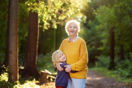 Loving grandson tenderly embracing his joyful elderly grandmother during walking at summer park. Two generations of family. Stok Fotoğraf
