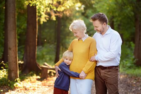 Beautiful eldery woman and her grown ups son, and her little grandson tenderly embracing together in park. Three generations of family