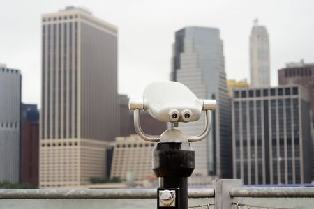 Binoculars looking to the Manhattan skyline over East River at rainy day. Shot with Brooklyn bridge park.
