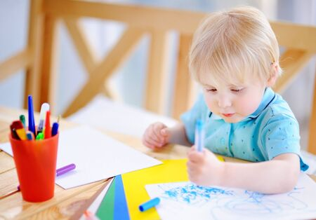 Cute little boy drawing and painting with colorful markers pens at kindergarten. Creative kid painting at playschool. educational classes on the Montessori system.