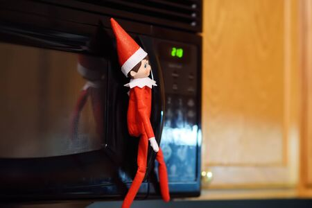 Funny Christmas toy elf on shelf near microwave. American christmas traditions. Elf is watching to see if the child behaves well. Xmas activities for family with kids.