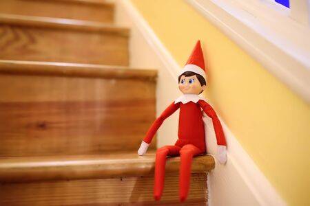 Funny Christmas toy elf on stairs. American christmas traditions. Xmas activities for family with kids. Banco de Imagens