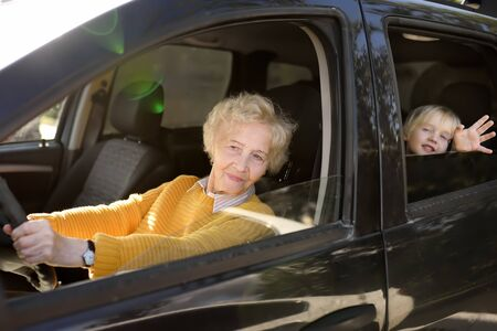 An elderly woman, grandmother or nanny, is driving a child in a car to kindergarten. Grandmothers upbringing. Stok Fotoğraf