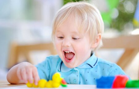 Creative boy playing with colorful modeling clay at kindergarten. Little kid molding at home. educational classes on the Montessori system