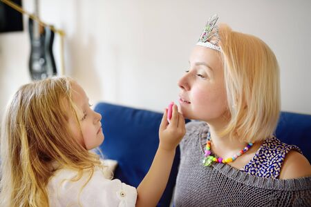 Young woman and her cute daughter playing beauty salon together. Little girl apply makeup for her mom. Loving mother and her preschooler girl playing together at home