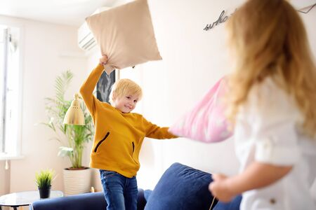 Pillow fight. Mischievous preschooler children jumping on a sofa and hitting each other with pillows. Boy and girl play together. Active games for siblings at home. Stock Photo