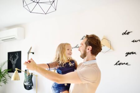 Young handsome father with his little curly hair daughter dancing at home. Loving dad and his preschooler girl playing together at home. Happy fatherhood