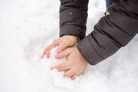 L'homme fait boule de neige. Plaisirs d'hiver en plein air. Gros plan sur les mains.