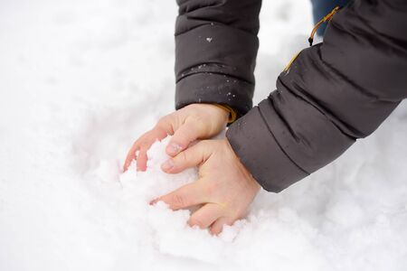 Man is making snowball. Winter fun outdoors. Hands close-up.