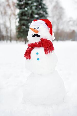 Handgemachter Schneemann mit Schal, Weihnachtsmannmütze, Karottennase und Schnurrbart in einem verschneiten Park. Aktive Outdoor-Freizeit für Kinder und Familie im Winter
