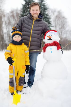 Little boy with his father building snowman in snowy park. Active outdoors leisure with children in winter. Kid during stroll in a snowy winter park Stock Photo