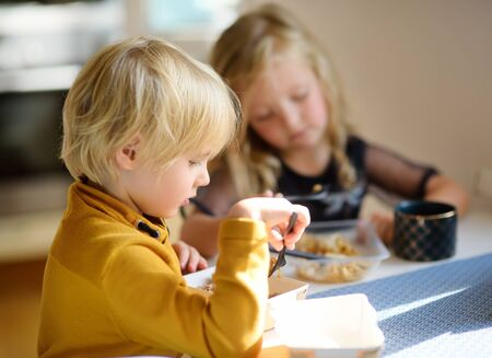 Preschoolers is eating fast or convenience foods in the kitchen at home. Nutrition of a modern family in a big city. Food delivery services. Lack of time. Banque d'images - 131690511