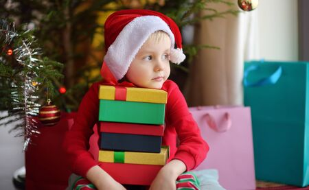 Cute little boy with a Christmas gift under fir tree at home. Portrait of frustrated kid in Christmas morning. Cozy living room with decorated fir tree Banque d'images - 131690633