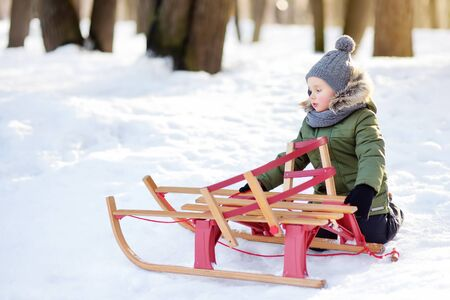 Cute little boy with broken sled on a walk in snowy park. Frustrated child tries to fix them. Trouble waiting on winter walks. Banque d'images - 131690649