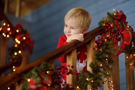 Little boy in decorated christmas house interior. Xmas mood.
