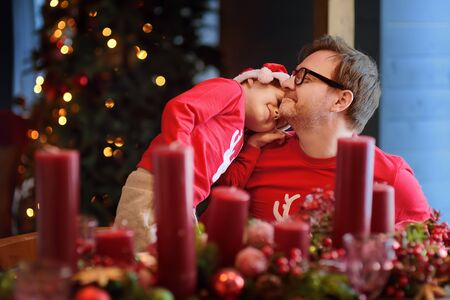 Little boy and his father enjoying christmas table set. Cozy living room with decorated fir tree. Holidays activities for family with kids. Eve Xmas. Stock Photo