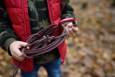 Little boy scout during hiking in autumn forest. Child is holding rope with hitch carbine. Concepts of adventure, scouting and hiking tourism for kids.
